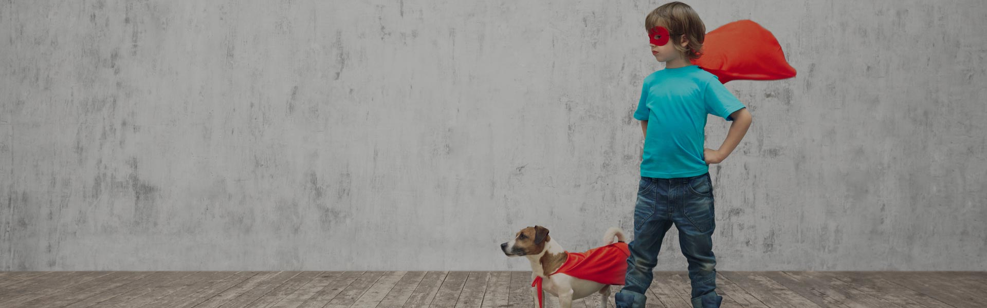 terrier and small child wearing capes making superhero poses